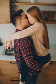 Attraktives junges kaukasisches paar, das sich am morgen in der küche küsst, während mann seine freundin auf seinen armen hält.