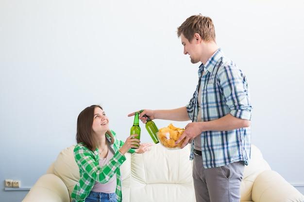 Attraktives junges liebespaar, das bier zu hause trinkt