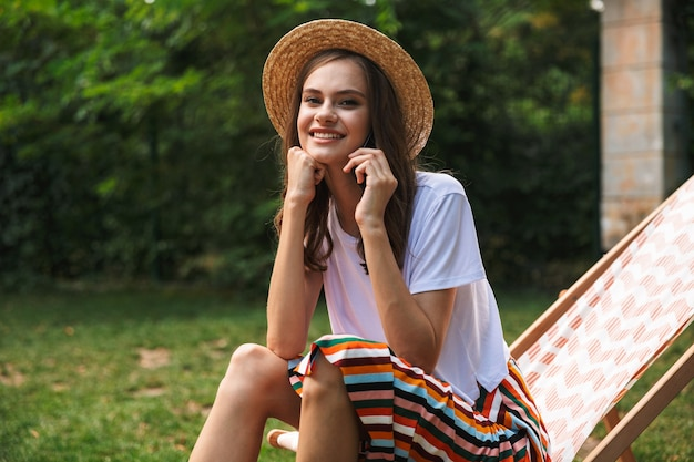 Attraktives junges mädchen, das auf einer hängematte am stadtpark draußen im sommer ruht