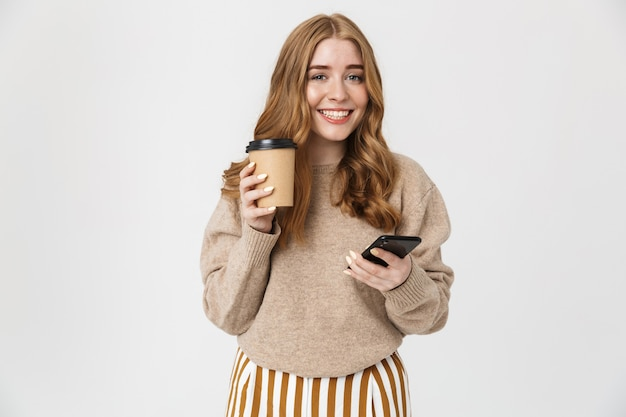Attraktives junges mädchen, das einen pullover trägt, der isoliert über einer weißen wand steht und kaffee zum mitnehmen trinkt, während er das handy benutzt