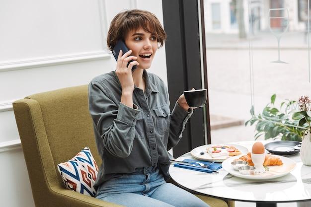 Attraktives junges mädchen, das im café drinnen frühstückt und mit dem handy spricht