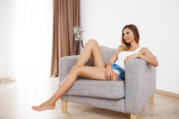 Attraktives junges mädchen, das im sessel am wohnzimmer sitzt und beiseite schaut