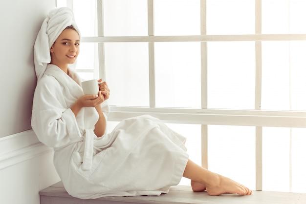 Attraktives junges mädchen im bademantel und mit einem tuch.
