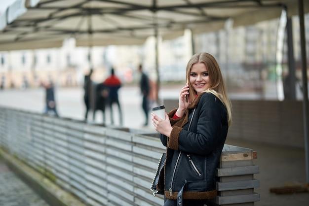 Attraktives junges mädchen. im park telefonieren. attraktive junge dame, die mit ihren freunden per handy plaudert und kaffee trinkt
