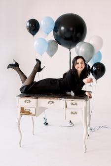 Attraktives junges mädchen im schwarzen kleid, das auf weißem weinlese-tisch liegt und das martini-glas auf weißem hintergrund hält. hübsches mädchen elebrating frohes neues jahr, geburtstagsfeierballons auf dem hintergrund