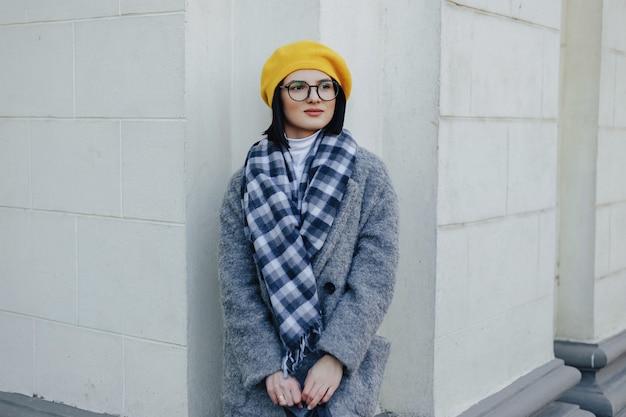 Attraktives junges mädchen in den gläsern im mantel und im gelben barett auf einem einfachen hellen hintergrund