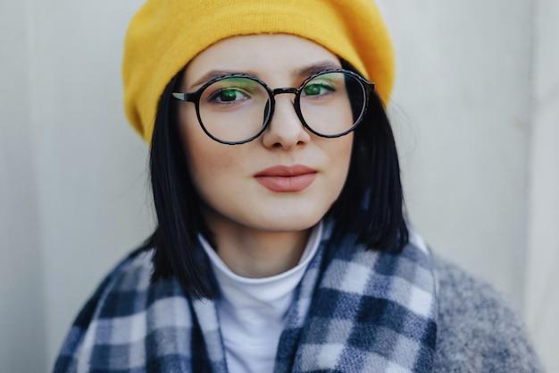 Attraktives junges mädchen in den gläsern im mantel und im gelben barett
