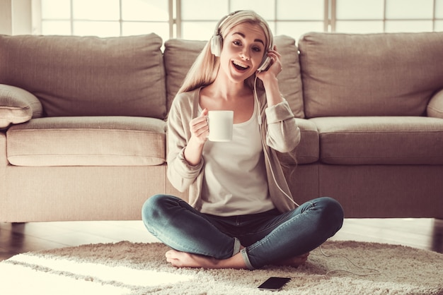 Attraktives junges mädchen in den kopfhörern hört musik.