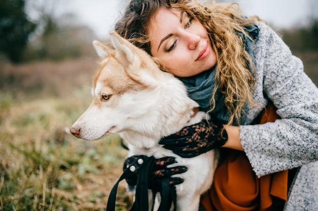 Attraktives junges mädchen mit dem gelockten haar und leidenschaftlichem emotionalem gesicht gehend mit ihrem heiseren welpen im freien in der landschaft. elegant gekleidete erwachsene schönheit umarmt mit inländischem reizendem hund. haustier liebhaber