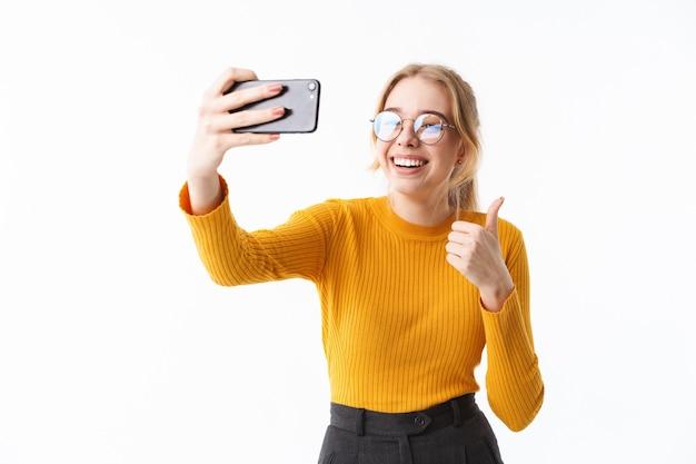 Attraktives junges mädchen mit pullover steht isoliert über weißer wand und macht ein selfie