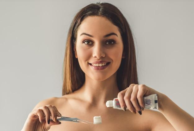 Attraktives junges mädchen trägt zahnpasta auf zahnbürste auf.