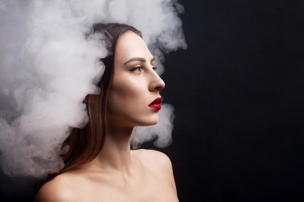 Attraktives junges mädchen und weißer rauch schwarzer hintergrund