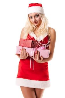 Attraktives junges mädchen verkleidet als weihnachtsmann-freundin, die eine schachtel mit einem geschenk in ihren händen hält, die auf einem weißen hintergrund im studio aufwirft