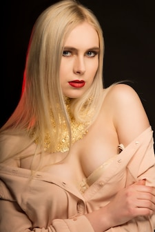 Attraktives junges model mit langen blonden haaren und goldener folie auf der haut, posiert mit nackten schultern