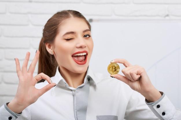 Attraktives junges modell, das goldenes bitcoin als hauptcryptocurrency hält und okayzeichen zeigt, während playfully zur kamera blinzelt.
