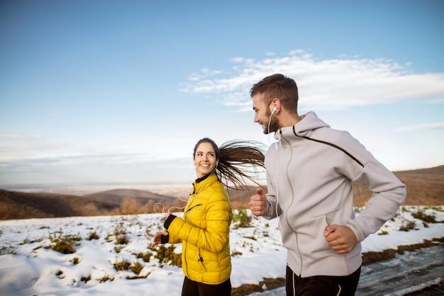 Attraktives junges paar, das an einem wintertag in der natur läuft.