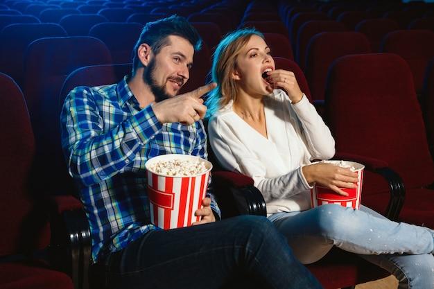 Attraktives junges paar, das einen film in einem kino sieht