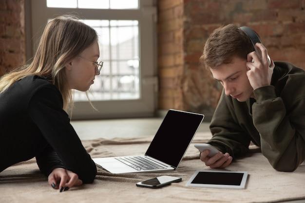 Attraktives junges paar, das geräte zusammen, tablet, laptop, smartphone, kabellose kopfhörer verwendet.