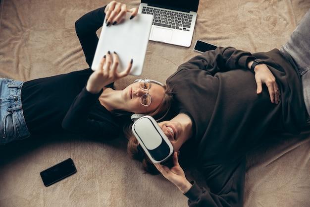 Attraktives junges paar, das geräte zusammen verwendet, tablette, laptop, smartphone, kopfhörer drahtlos. kommunikation, gadgets-konzept. technologien, die menschen in selbstisolierung verbinden. lebensstil zu hause.