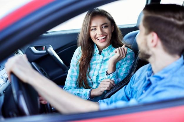 Attraktives junges paar, das im auto sitzt und einander ansieht, lächelnd, glücklich, porträt.