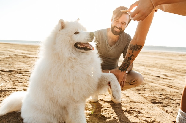 Attraktives junges paar, das mit ihrem hund am sonnigen strand spielt