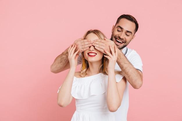Attraktives junges paar, das zusammen isoliert über rosa steht, augen bedecken