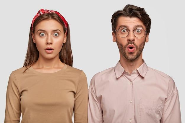 Attraktives junges paar mit schockiertem ausdruck, der gegen die weiße wand aufwirft