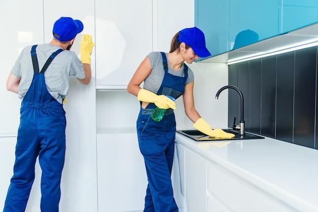 Attraktives junges paar von mann und frau in blauer uniform, die die möbel mit tüchern und spray in der komfortablen küche säubert