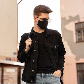Attraktives junges stylisches mannmodell in stylischer jeansjacke mit rucksack in vintage-sonnenbrille in schwarzer trendiger schutzmaske