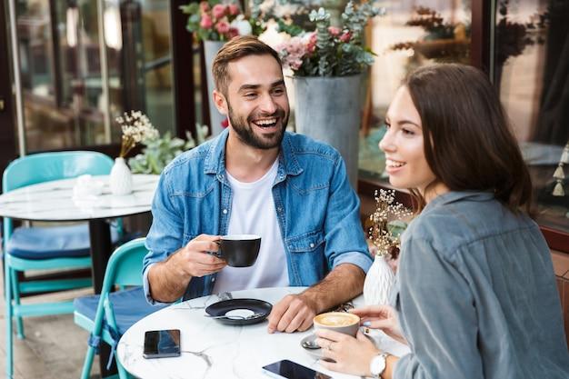 Attraktives junges verliebtes paar beim mittagessen beim sitzen am café-tisch im freien, kaffee trinken, reden
