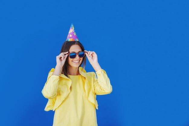 Attraktives kaukasisches junges mädchen in der gelben bluse und mit der geburtstagskappe auf dem kopf, der auf brillen setzt