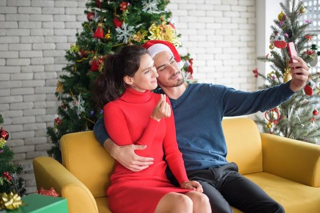 Attraktives kaukasisches liebespaar feiert weihnachten zu hause und telefoniert per smartphone mit der familie