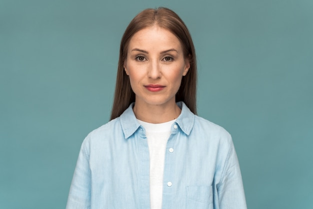 Attraktives kaukasisches mädchen mit weißem t-shirt und jeanshemd, das direkt in die kamera schaut. junge frau, die auf einem blauen wandhintergrund aufwirft
