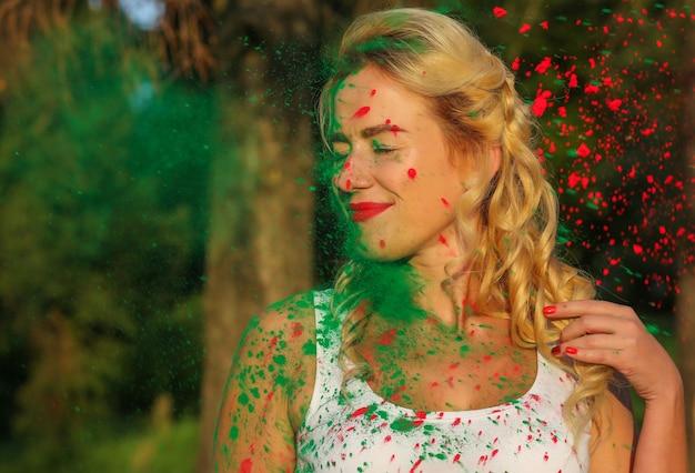 Attraktives kaukasisches modell mit langem, gewelltem haar, das mit farbspritzer einer trockenen holi-farbe posiert