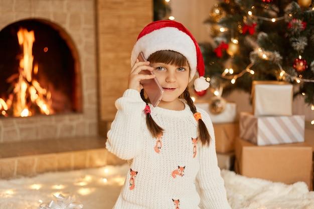 Attraktives kind, das weißen pullover und weihnachtsmannhut spricht telefon im festlichen raum trägt