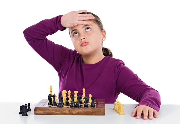Attraktives kleines mädchen, das schach auf über weißem hintergrund spielt