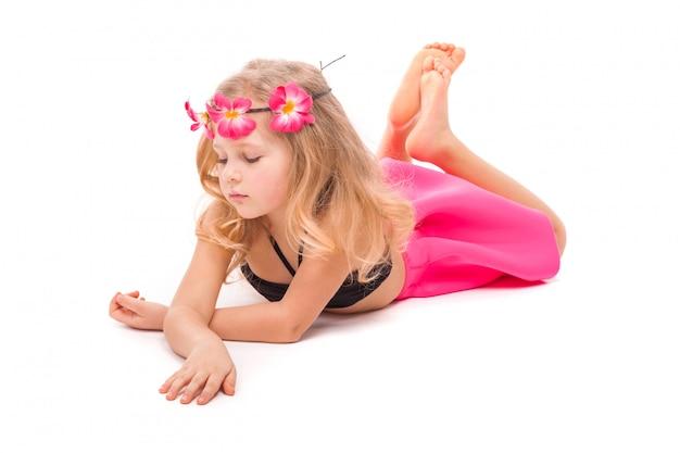 Attraktives kleines mädchen im schwarzen bikini, im rosa rock und im rosa kranz, lügen