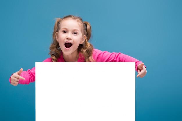 Attraktives kleines nettes mädchen im rosa hemd mit affen und blauer hose halten leeres plakat
