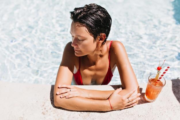 Attraktives kurzhaariges weibliches modell, das fruchtcocktail im pool genießt