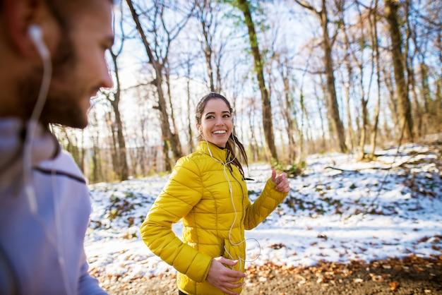 Attraktives lächelndes fit sportliches paar, das im wintermorgen mit kopfhörern durch den wald läuft.