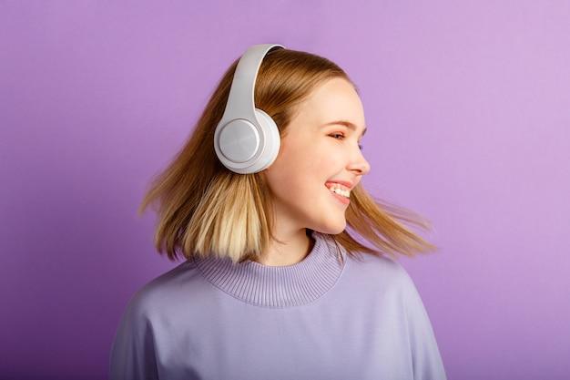 Attraktives lächelndes frauentanzen in den kopfhörern mit fliegender blonder haarfrisur. teenager-mädchenporträt, das seite schaut, genießen sie musik, die sich in kopfhörern bewegt, die über violettem farbhintergrund isoliert sind.