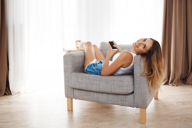 Attraktives lächelndes junges mädchen, das im sessel liegt und im wohnzimmer plaudert.