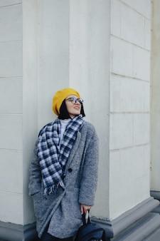 Attraktives lächelndes junges mädchen in den gläsern im mantel und im gelben barett auf einem einfachen hellen hintergrund