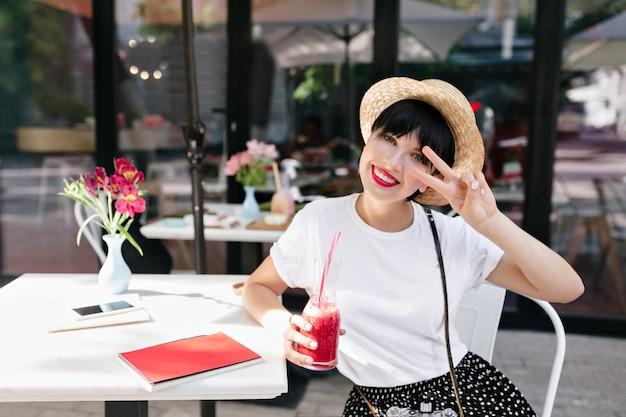 Attraktives lächelndes mädchen mit blasser haut, die mit vergnügen aufwirft, während sie im sommertag limonade trinkt