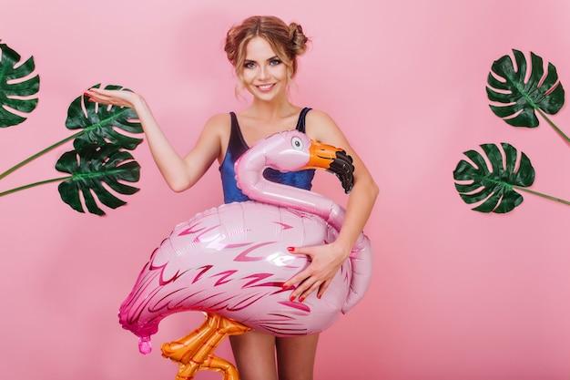 Attraktives lächelndes mädchen mit dem reizenden gesicht, das großen aufblasbaren flamingo hält und mit der hand oben steht. wunderschöne junge frau in der samtkleidung, die mit grünen pflanzen auf rosa hintergrund aufwirft