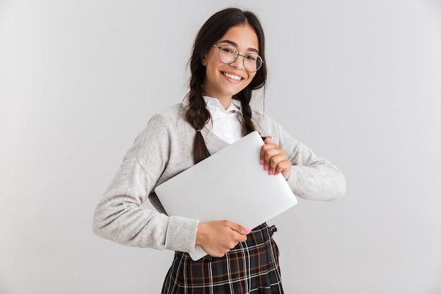 Attraktives lächelndes schulmädchen, das unifrom stehend über weißer wand trägt und laptop trägt