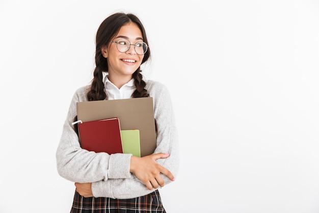 Attraktives lächelndes schulmädchen, das unifrom steht, das isoliert über weißer wand steht und lehrbücher trägt