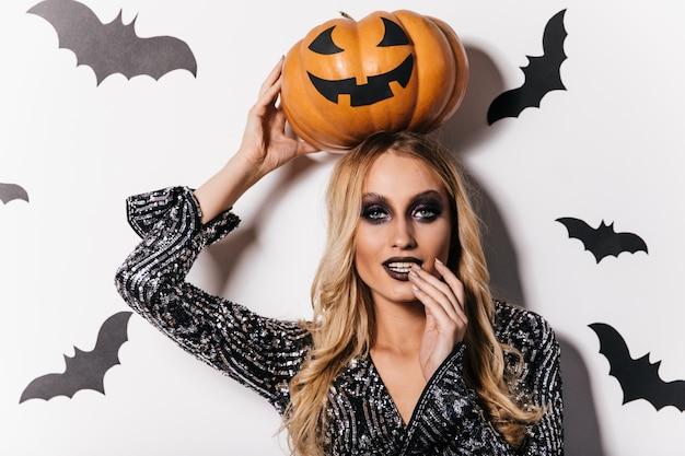 Attraktives langhaariges mädchen, das auf weißer wand mit fledermäusen steht. innenfoto des ansprechenden vampirs mit halloween-kürbis.