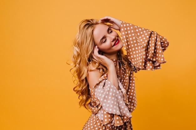 Attraktives langhaariges mädchen im braunen kleid, das erstaunliches lockiges weibliches modell aufstellt, das in der gelben wand tanzt.