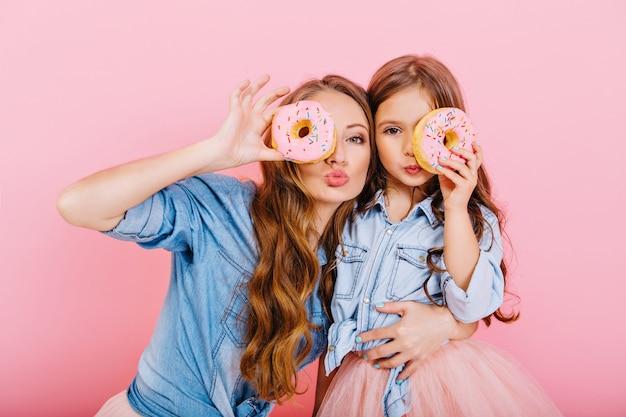 Attraktives lockiges mädchen im jeanshemd, das kleine schwester und lustiges aufstellen mit köstlichem donut auf rosa hintergrund umarmt. stilvolle langhaarige mutter und süße tochter, die spaß haben, donuts als brille zu halten